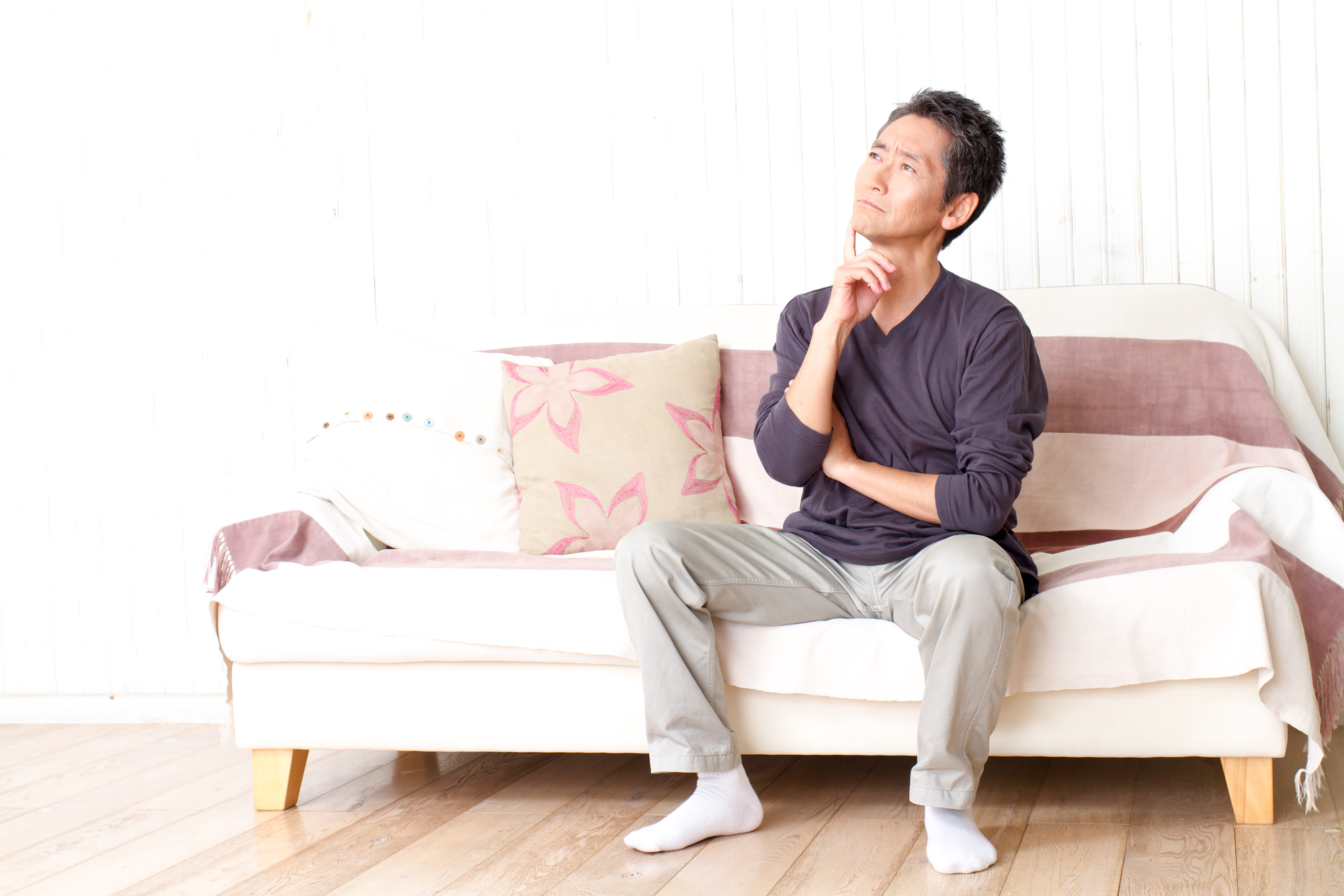 ソファに座って悩む男性