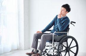 車いすに乗って悩む男性